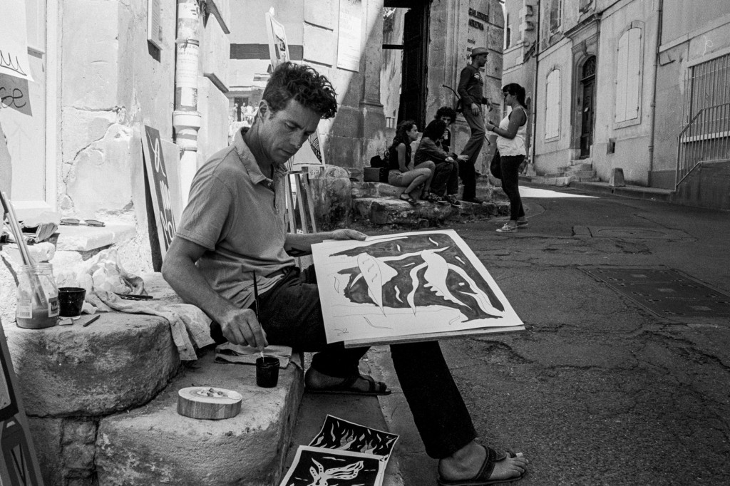A painter on the street below the Arles School of Photography.